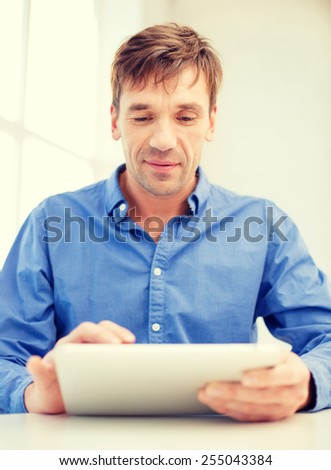 technology and lifestyle, distance learning concept - handsome man working with tablet pc at home - stock photo