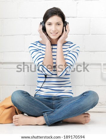 technology and music concept - picture of happy teenage girl in big headphones - stock photo