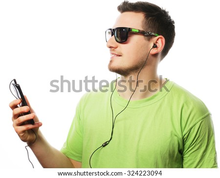 technology and people concept - young man wearing green t-shirt  listening music and using smartphone, isolated on white - stock photo