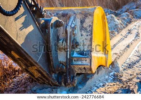 Technology and transport. Close-up of excavator bucket frozen sand and snow. Modal sun, warm light, long shadows. - stock photo