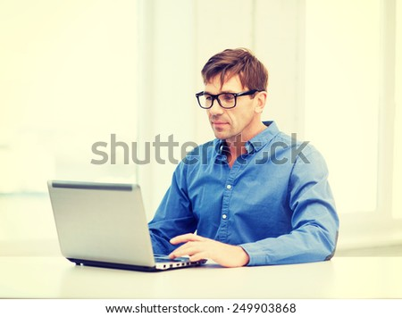 technology, business and lifestyle concept - man in eyeglasses working with laptop at home - stock photo