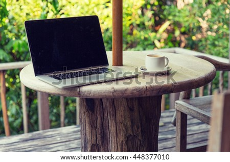 technology, business and modern life concept- close up of open laptop computer and coffee cup on table at hotel terrace