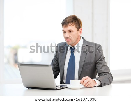 technology, business and office concept - handsome businessman working with laptop computer