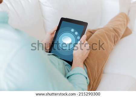 technology, business, leisure and people concept - close up of man holding tablet pc computer with text bubble icon on screen sitting on sofa at home - stock photo