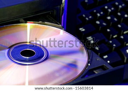 Technology concept by compact disc in focus and blurred keyboard in background.