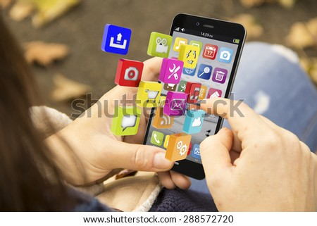 technology concept: young woman with downloading 3d generated phone at the park. Screen Graphics are made up. - stock photo