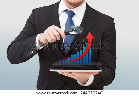 technology, development, analytics , people and business concept - close up of businessman holding magnifying glass over tablet pc computer and growth chart - stock photo