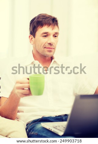 technology, drinks and lifestyle concept - man working with laptop at home, holding a cup of warm tea or coffee