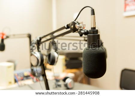 technology, electronics and audio equipment concept - close up of microphone at recording studio or radio station - stock photo