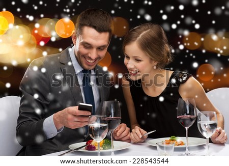 technology, food, christmas, holidays and people concept - smiling couple with smartphone eating at restaurant over night lights background - stock photo