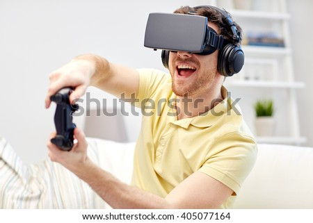 technology, gaming, entertainment and people concept - happy young man with virtual reality headset or 3d glasses with controller gamepad playing racing video game at home - stock photo