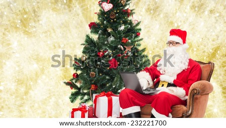 technology, holidays and people concept - man in costume of santa claus with laptop computer, gifts and christmas tree sitting in armchair over yellow lights background