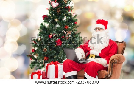 technology, holidays and people concept - man in costume of santa claus with laptop computer, gifts and christmas tree sitting in armchair over lights background