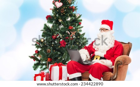 technology, holidays and people concept - man in costume of santa claus with laptop computer, gifts and christmas tree sitting in armchair over blue lights background