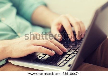 technology, home and lifestyle concept - close up of man working with laptop computer and sitting on sofa at home - stock photo