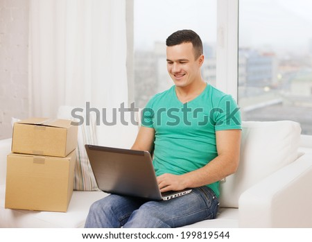 technology, home and lifestyle concept - smiling man with laptop and cardboard boxes at home - stock photo