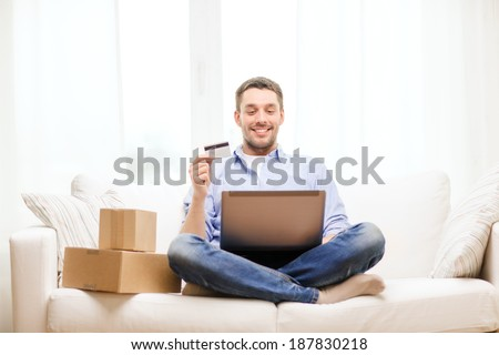 technology, home and lifestyle concept - smiling man with laptop, credit card and cardboard boxes at home - stock photo