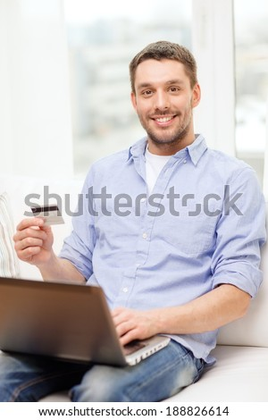 technology, home and lifestyle concept - smiling man working with laptop and credit card at home - stock photo