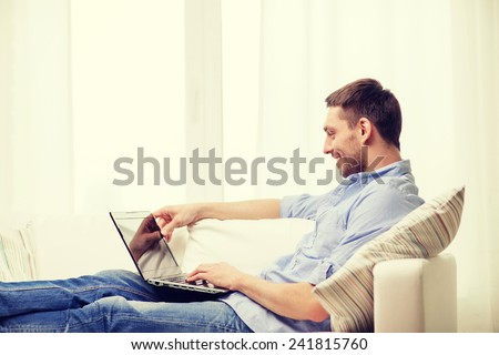 technology, home and lifestyle concept - smiling man working with laptop at home - stock photo
