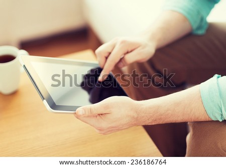 technology, home, drinks and lifestyle concept - close up of man with tablet pc computer and cup of coffee at home