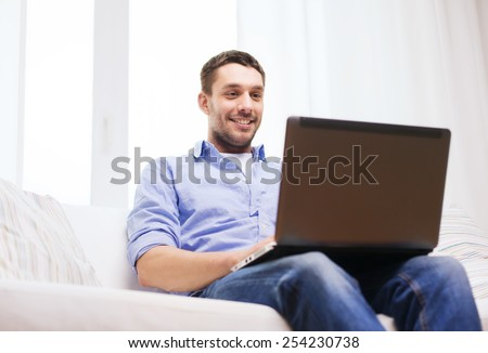 technology, home, people and lifestyle concept - smiling man working with laptop at home