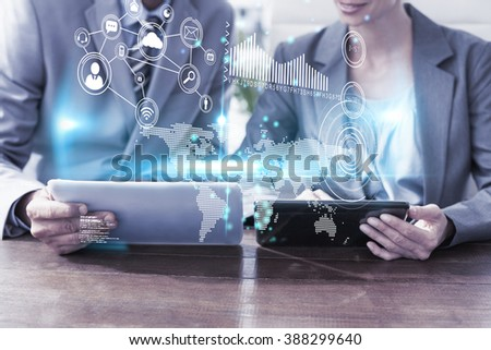 Technology interface against business people discussing over tablet pcs - stock photo