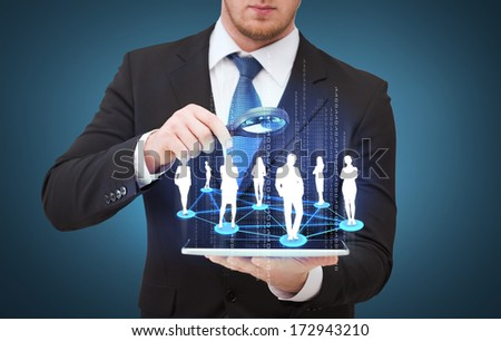 technology, internet and business concept - businessman holding magnifying glass over tablet pc and looking at social or business network - stock photo