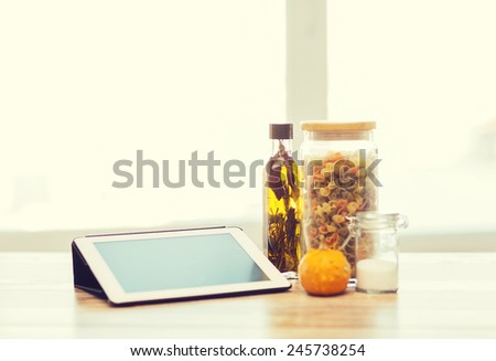 technology, internet and cooking concept - close up of tablet pc computer, olive oil, pasta, salt and pumpkin - stock photo