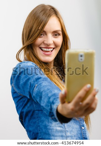 Technology internet and happiness concept. Young fashion woman in denim shirt taking self picture selfie with smartphone camera