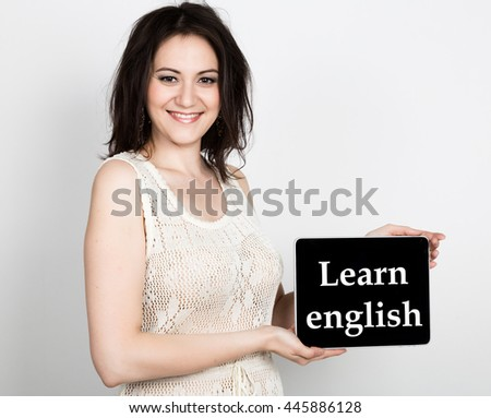 technology, internet and networking - close-up successful woman holding a tablet pc with learn english sign. internet technology in tourism