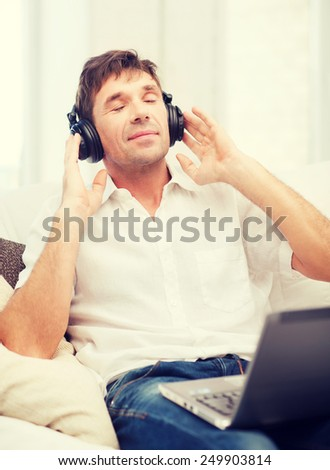 technology, leisure and lifestyle concept - happy man with headphones listening to music at home - stock photo