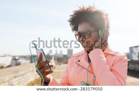 technology, lifestyle and people concept - smiling african american young woman or teenage girl with smartphone and headphones listening to music outdoors - stock photo