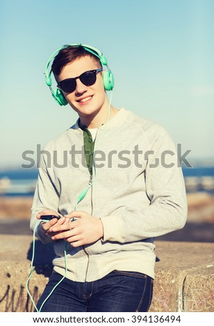 technology, lifestyle and people concept - smiling young man or teenage boy in headphones with smartphone listening to music outdoors - stock photo