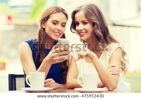 technology, lifestyle, friendship and people concept - happy young women or teenage girls with smartphone and coffee cups at outdoor cafe