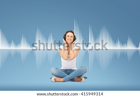technology, music and happiness concept - smiling young woman or teen girl in headphones over blue background and sound wave or diagram - stock photo