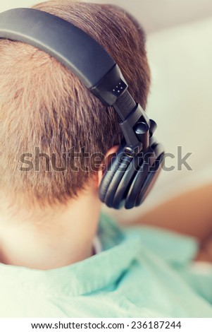 technology, music, leisure and happiness concept - close up of man in headphones at home from back - stock photo