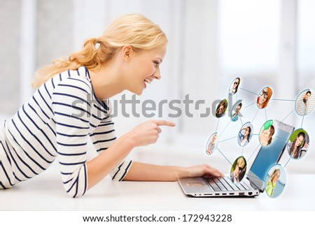 technology, networking and internet concept - smiling student girl pointing her finger at laptop screen in college - stock photo