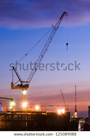 technology of transport by Derrick crane on construction site in the city at sunset time, Bangkok, Thailand - stock photo