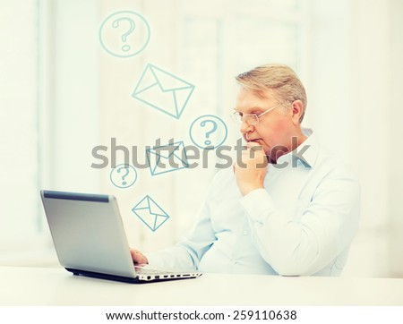 technology, oldness and lifestyle concept - old man in eyeglasses working with laptop computer at home - stock photo