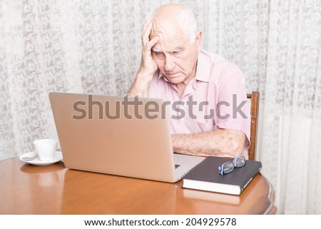 technology, oldness and lifestyle concept - old man in working with laptop computer at home concerned