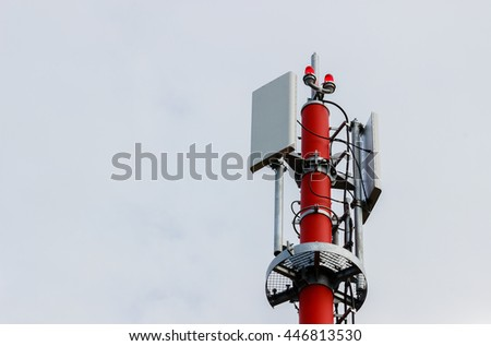 Technology on the top of the GSM tower (telecommunication antenna, transmitter), red and white striped pole, blue sky, white clouds. - stock photo