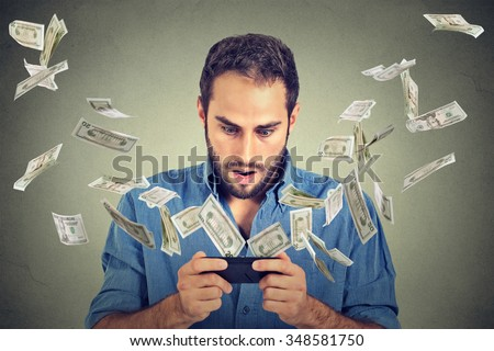 Technology online banking money transfer, e-commerce concept. Shocked young man using smartphone with dollar bills flying away from screen isolated on gray wall office background. - stock photo