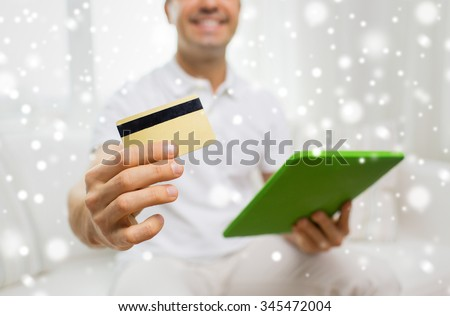 technology, people and lifestyle, distance learning concept - close up of happy man with credit card and tablet pc computer at home over snow effect - stock photo