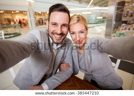 technology, photographing, and people concept - happy couple taking selfie with smartphone or camera on mall - stock photo
