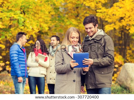 technology, season, friendship and people concept - group of smiling men and women with tablet pc computers in autumn park - stock photo