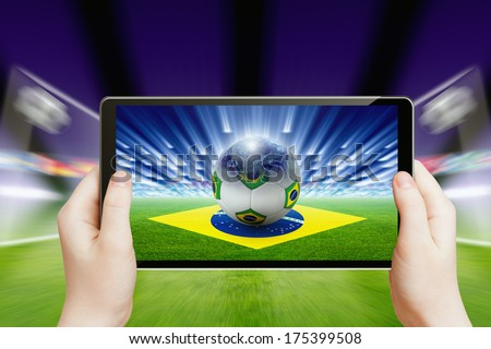 Technology, sports background - tablet pc in hands, soccer ball, sports game online concept, brazil flag.  Elements of this image furnished by NASA