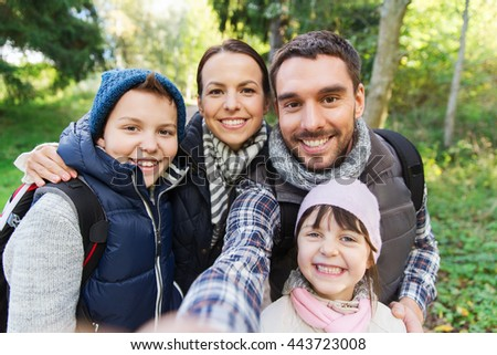 technology, travel, tourism, hike and people concept - happy family with backpacks taking selfie and hiking