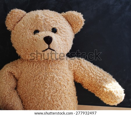 Teddy bear alone against the black board as if giving its hand to the viewer