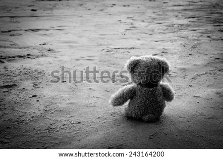Teddy bear alone sit in beach ,sad concept black and white photography