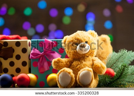 Teddy bear and christmas gifts with fairy lights on background